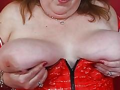 Mature fat momma in corset sticks dildo up her nookie on bed